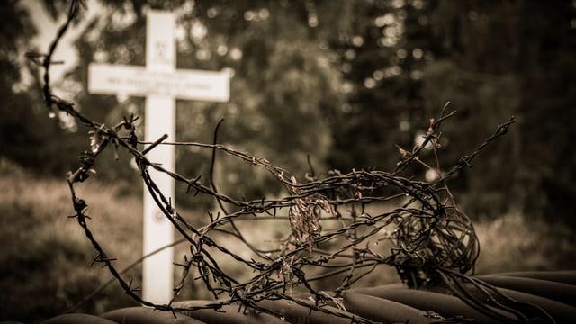 Ein Stacheldrahtgewirr, dahinter ein weisses Kreuz.