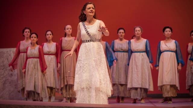 Eine Frau in weissem Gewand singt vor einem Frauenchor ebenfalls in weissen Gewändern