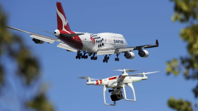 Ein Flugzeug und eine Drohe fliegen am Himmel.