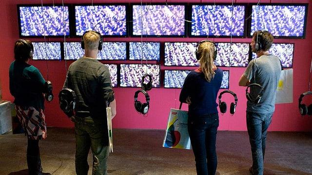 Menschen vor Bildschirmen, die an einer Wand hängen