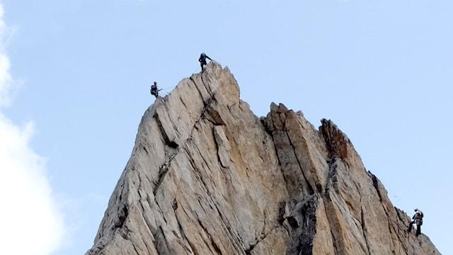 Ein Berggipfel, von verschiedenen Seiten her klettern Bergsteiger zum Gipfel.