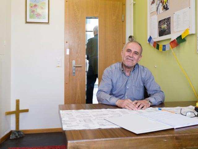 Ein mann sitzt an einem Schreibtisch. Neben ihm sieht man ein Kreuz und farbige Fahnen.