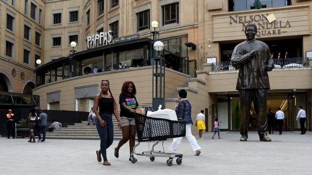 Frauen mit Einkaufswagen vor einem Shopping Center