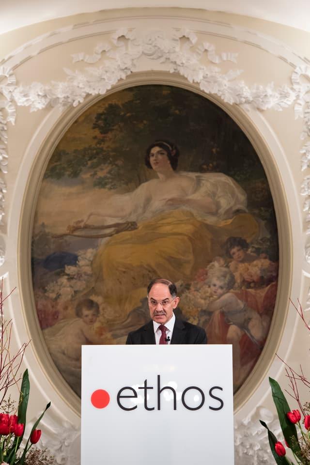 Biedermann am Redner-Pult. Im Hintergrund ein riesiges Gemälde mit einer mythologischen Frauenfigur.