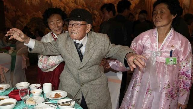 Der alte Mann im grauen Anzug tänzelt zwischen seinen Nichten in weissen Kimonos gekleidet.