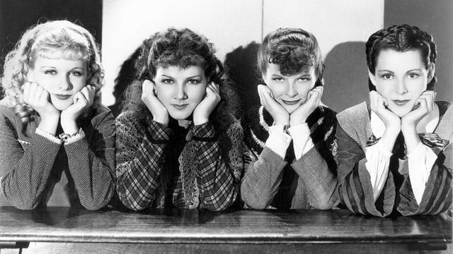 Vier Frauen stützen ihr Gesicht mit beiden Händen und blicken in die Kamera.