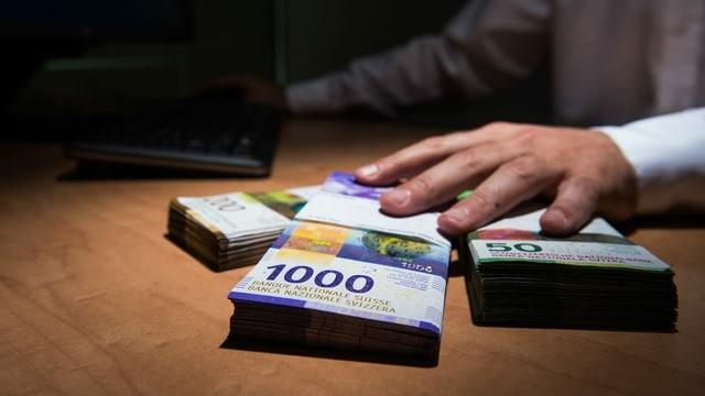 Symbolbild: Eine hand greift nach Geldbündeln.