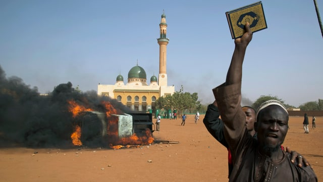 Ein Mann hält neben einem brennenden Auto vor einer Moschee in Niamey einen Koran in die Höhe. (reuters)