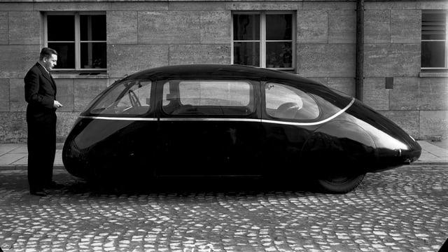 Ein Mann steht neben dem Göttinger Ei genannten windschnittigen Auto (Schwarz-Weiss-Foto)