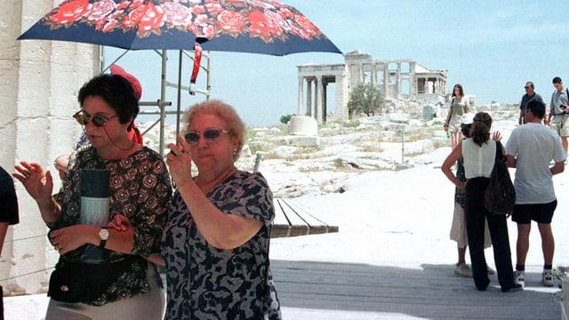 Duas turistas sut in parisol avant l'Acropolis.