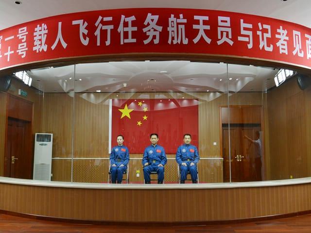Drei Astronauten sitzen nebeneinander auf Stühlen in einem Glaskasten mit chinesischen Schriftzeichen.