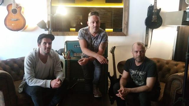 Sandro Dietrich, Lou «Geniuz» Zarra e Stefan «Stämpf» Schmid sesan sin il canapé en lur studio Klangstark a Cuira.