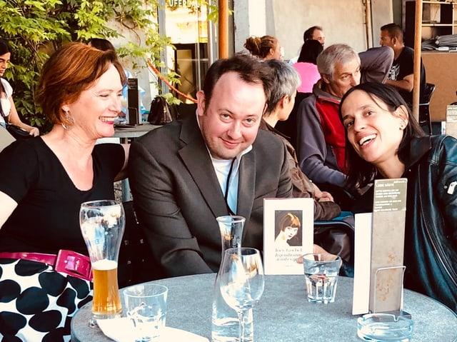 Joe Goebel, Ruth Geiger und Annette König sitzen an einem Tisch und lachen in die Kamera