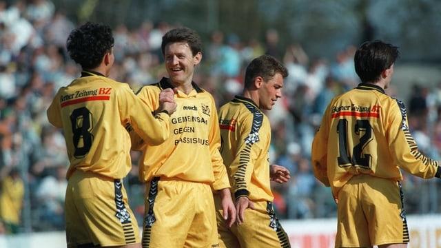 Vier männliche Fussballspieler in gelben Trikots mit der Aufschrift «Gemeinsam gegen Rassimus».