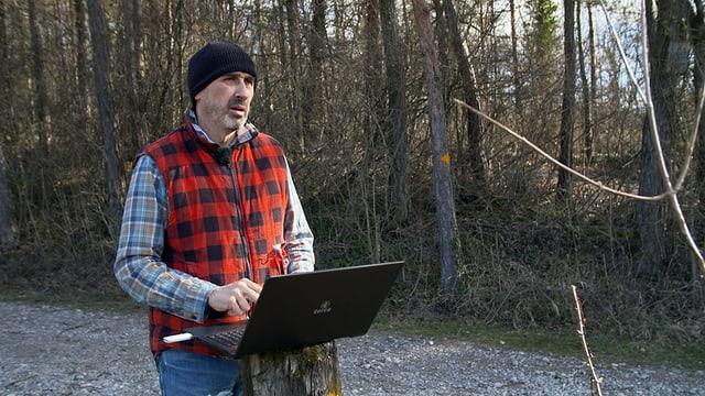 Ein Mann steht mit Laptop im Wald.
