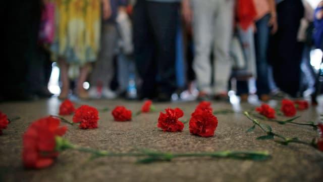 Rote Blumen liegen als Zeichen der Trauer auf dem Boden.