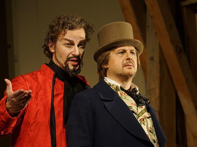 Zwei Schauspieler, einer mit roter Robe, der andere mit altertümlichem Hut