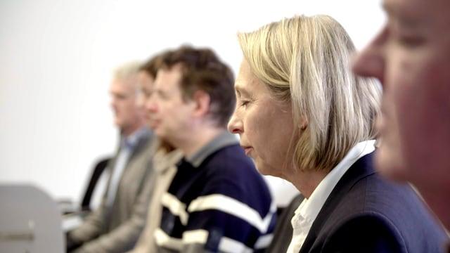 Angelika von der Assen sitzt mit geschlossenen Augen neben Mitarbeitern beim Meditieren.