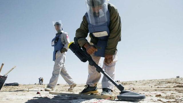 Ein Arbeiter im Schutzanzug sucht eine karge Landschaft nach Minen ab.