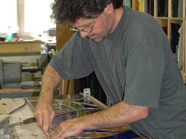 Mann schneidet Glasstücke.
