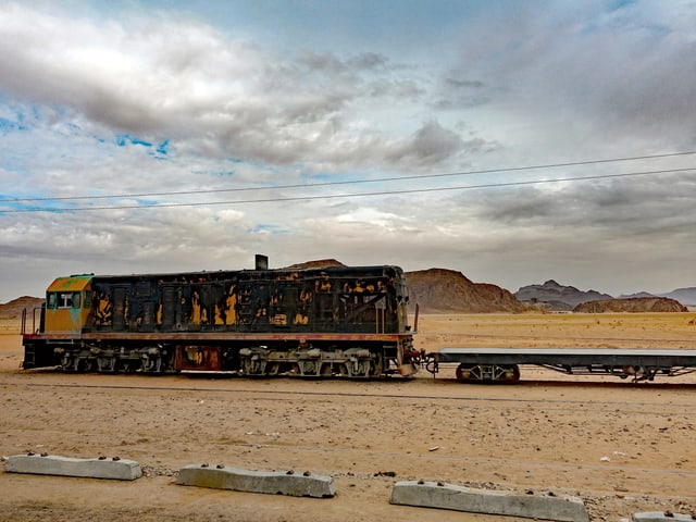 Eine alte Güter-Lokomotive mit abblätternder Farbe steht in einer Wüste. Im Hintergrund sieht man weit entfernt Felsen.