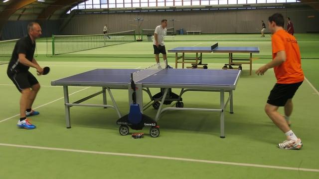 In einer Tennishalle spielen Spieler an Tischtennistischen, im Hintergrund spielen sie Tennis.