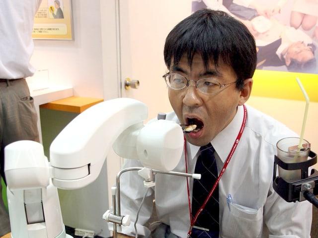 Ein Japaner sitzt mit offenem Mund vor einer weissen Maschine, die ihm einen Happen Essen in den Mund schiebt.