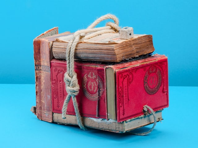 Roter Apparat aus Büchern vor blauem Hintergrund