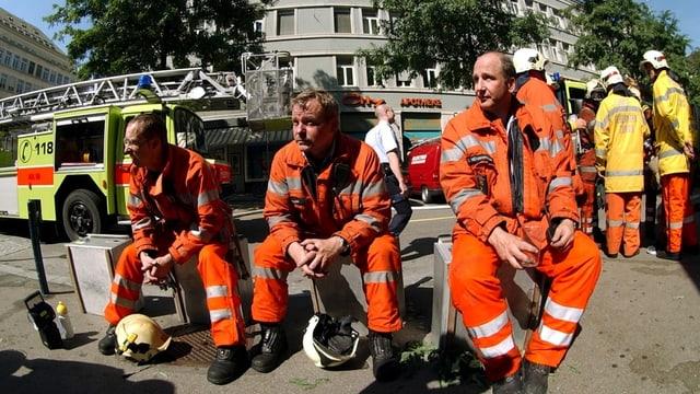 Drei Feuerwehrleute in organgen Uniformen sitzen auf einer Bank. Im Hintergrund ein Feuerwehrauto.