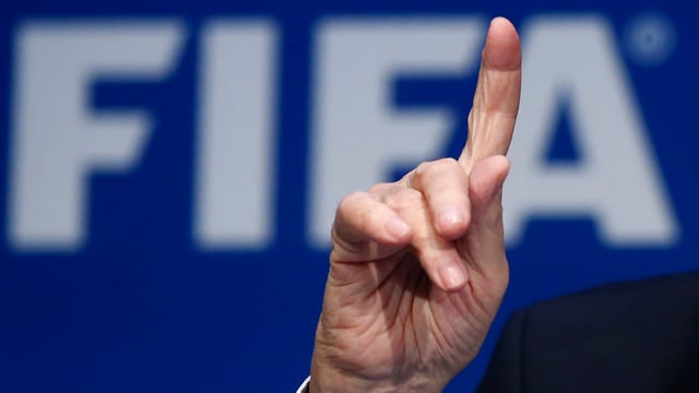 Hand mit ausgestrecktem Zeigefinger vor Fifa-Logo