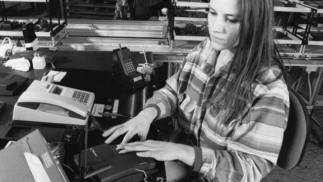 Eine Frau fast ein Festnetztelefon an
