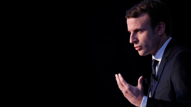 Macron von der Seite aufgenommen, vor schwarzem Hintergrund.