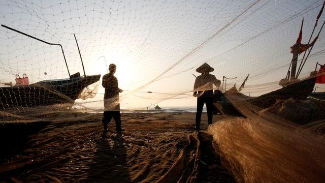 Fischer spannen ihre Netze am Strand auf