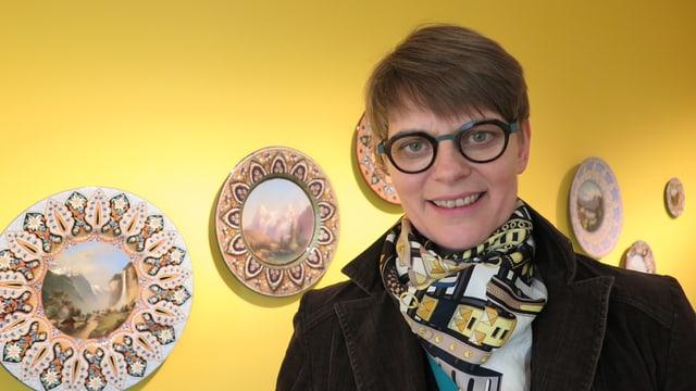 Lilian Raselli vor Veduttentellern an der Wand