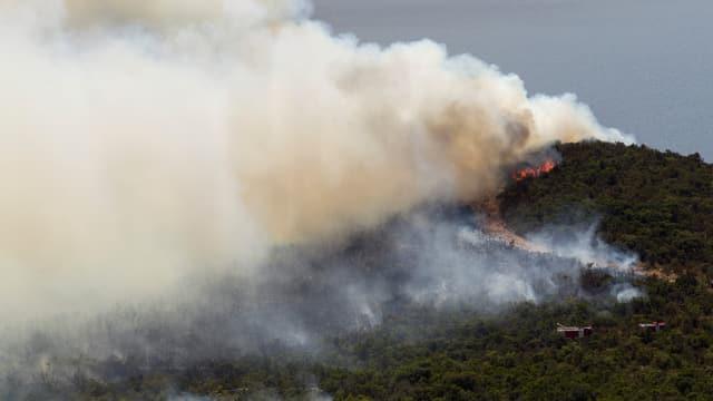 Bewaldeter Hügel, es brennt und raucht.
