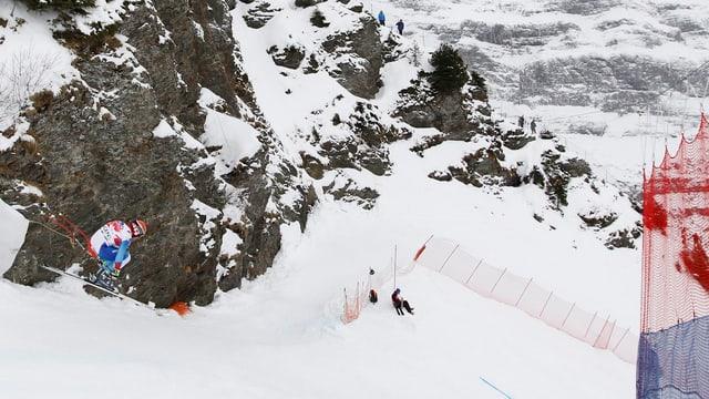 Das Bild zeigt den felisgen Hundschopf und ein Skifahrer, der in der Luft schwebt.