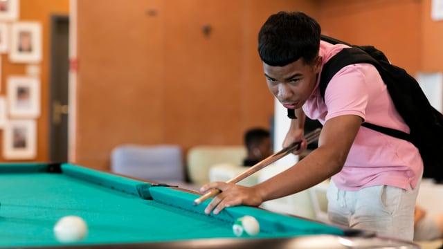 Ein junger Mann an einem Billiard.