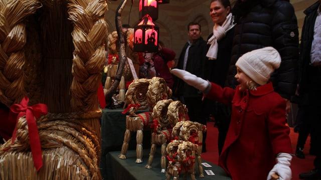 Estelle zeigt auf einen Stroh-Julbock.