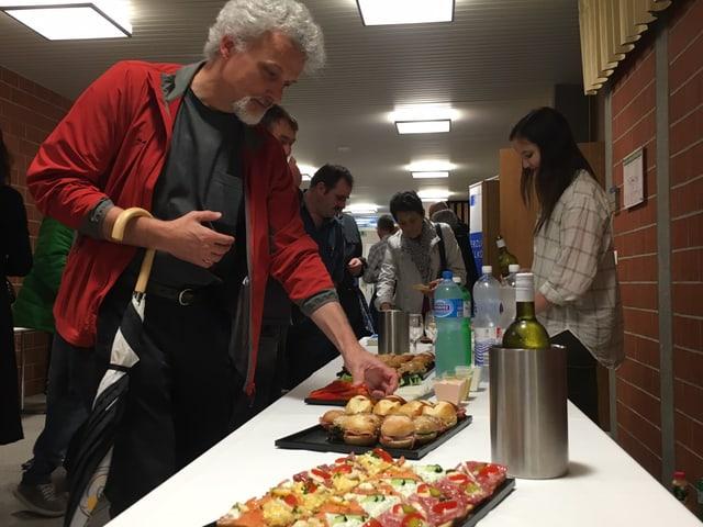 Ein langer Tisch mit Canapés, Sandwich und Getränken. Ein Mann mit Schirm am Arm greift zu einer Serviette.