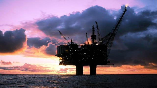 Aufnahme einer Ölplattform im Ozean, im Hintergrund sind schwarze Wolken am Himmel.