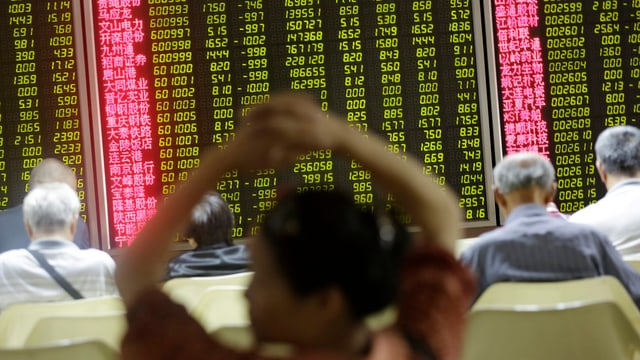 Im Hintergrund Börsendaten – im Vordergrund Rückenansichten von Chinesen