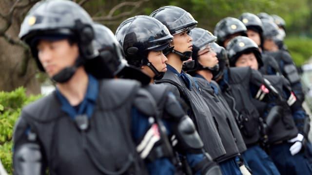 Polizisten in schwarzen Uniformen mit Helm.