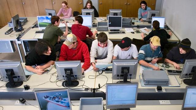 Männliche Teenager arbeiten an mehreren Computern in einem Schulraum