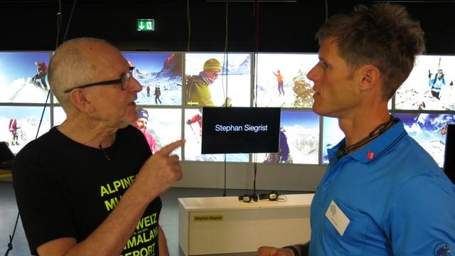 Stephan Siegrist steht mit einem Ausstellungsmacher im Alpinen Museum vor einer Videowand.