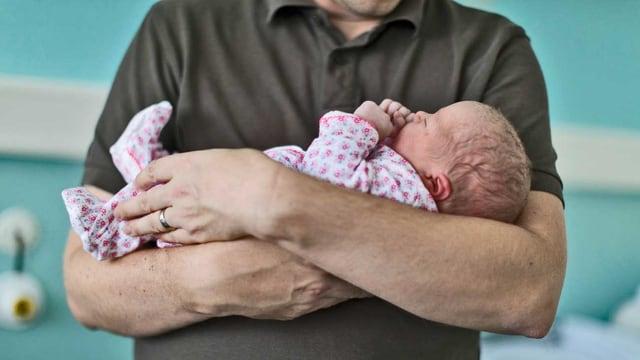 Ein Vater hält seinen Frischling in den Armen.