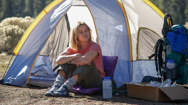 Reese Witherspoon sitzt in der Wildnis vor ihrem Zelt.