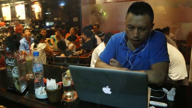 Ein Vietnamese sitzt in einem Restaurant in Hanoi vor einem Laptopp und surft im Internet.