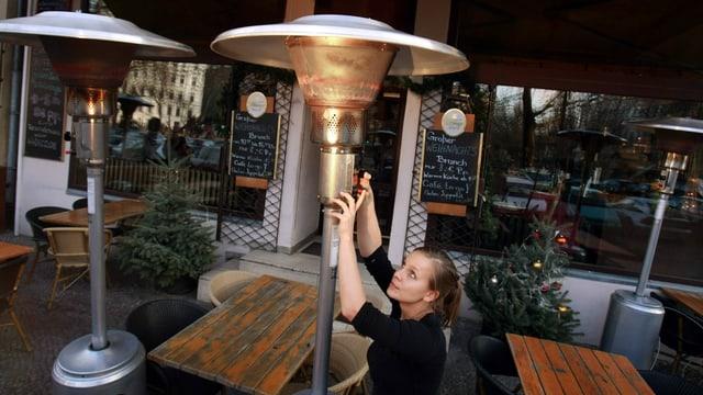 Angestellte bedient Heizpilz in deutschem Restaurant