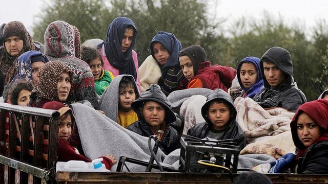 Kinder und Frauen sitzen in einem Wagen in Afrin.