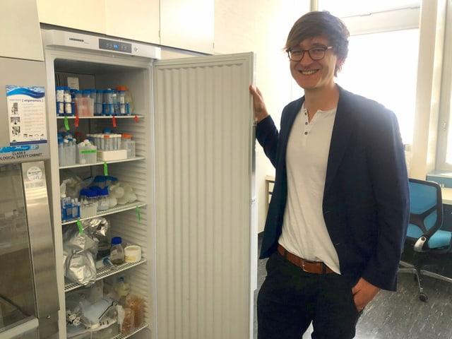 Stefan Halbherr steht vor einem geöffneten Kühlschrank